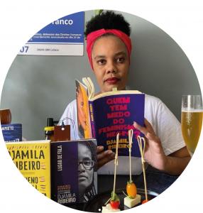 Sara segura um livro de Djamila Ribeiro, a frente dela vemos mais um livro da autora, alguns petiscos e uma taça com cerveja.